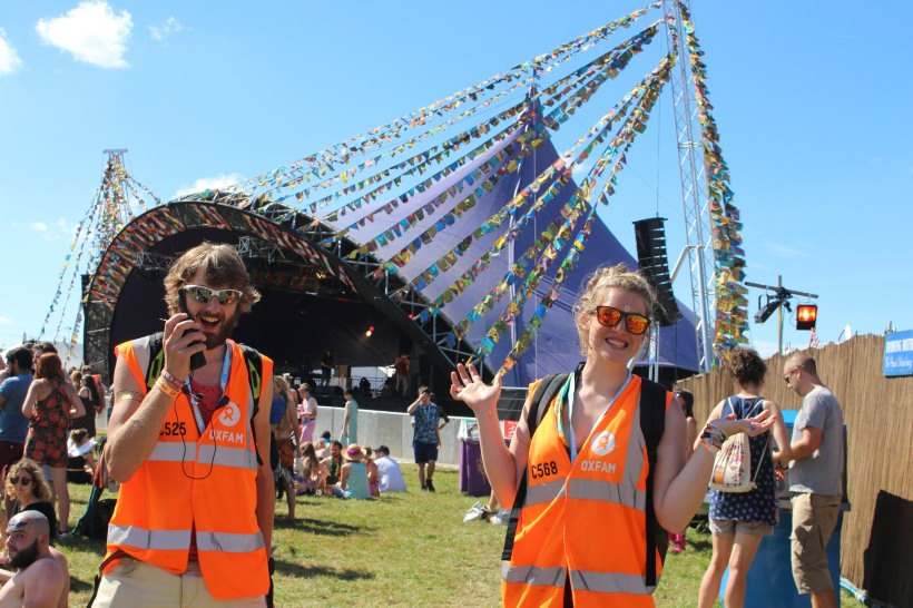 Two happy Oxfam Stewards in the sunshine at Shambala festival stewarding volunteers volunteering