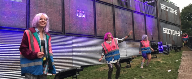 Boomtown Volunteers dancing at the front of Sector 6 in fantastic coloured wigs