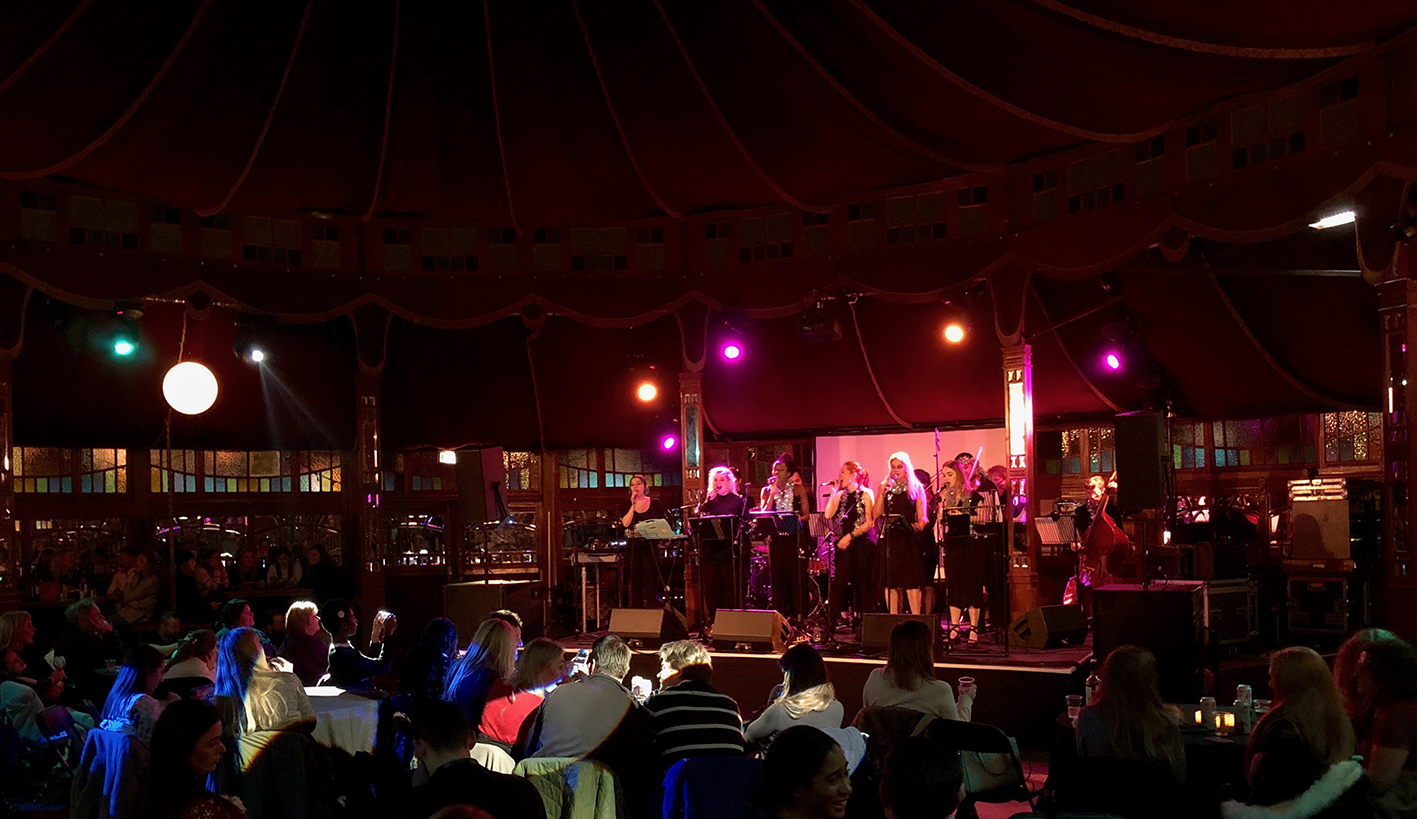The Winterville Choir performing in the Spiegeltent wearing tinsel in front of an orchestra