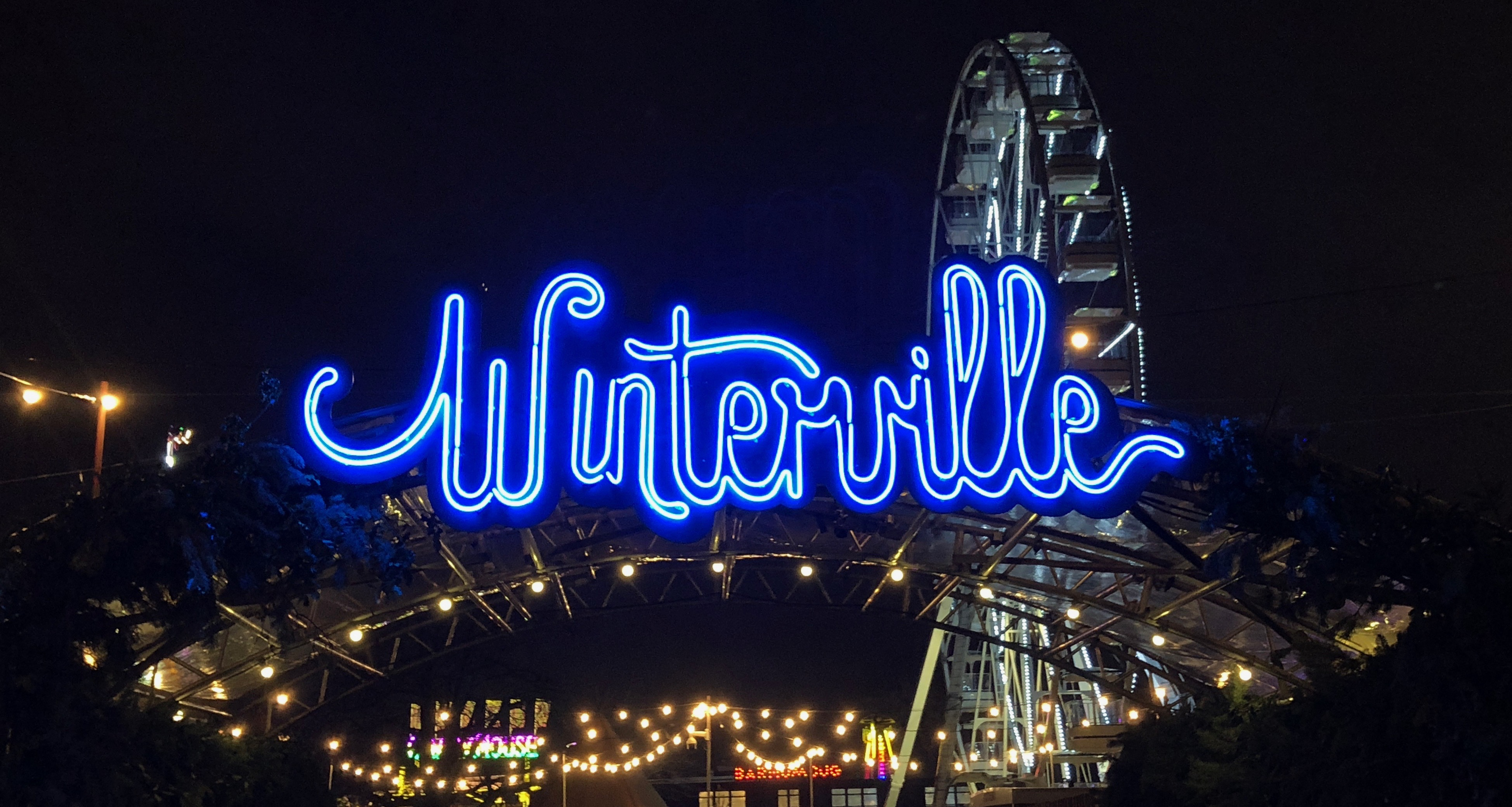 The neon Winterville sign at the entrance to the festival with the big wheel in the background