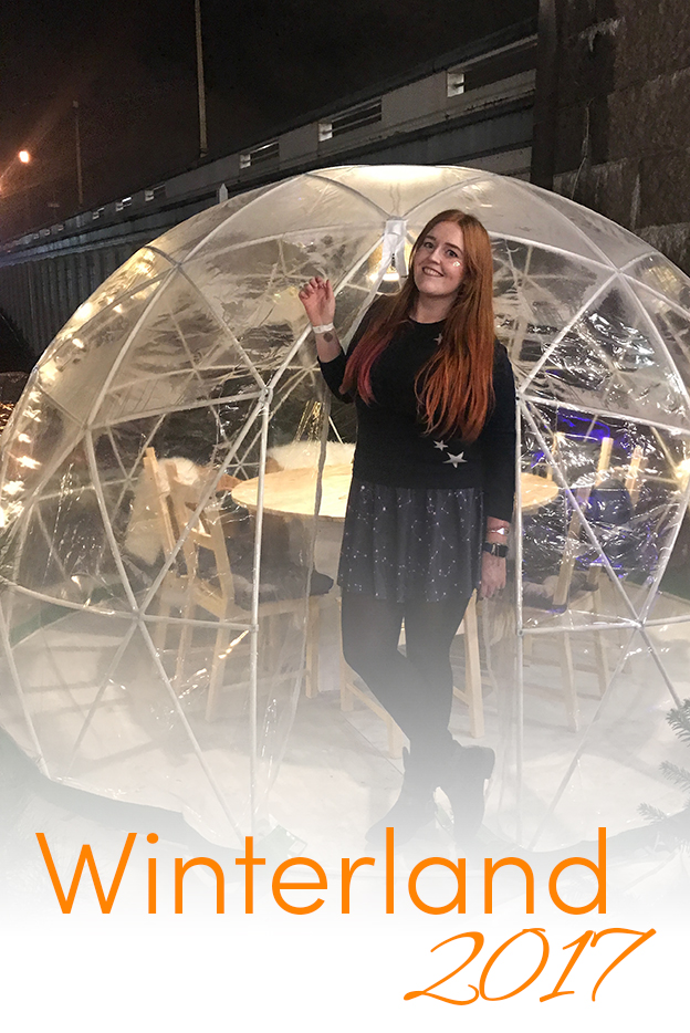 Pinterest share image - me stood infant of one of Winterland's lovely heated igloos with blog title winter festival London